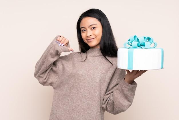 Nastolatek azjatycka dziewczyna trzyma dużego tort odizolowywający na beżowej ścianie dumnej i samozadowolonej
