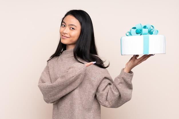 Nastolatek azjatycka dziewczyna trzyma dużego tort odizolowywający na beżu