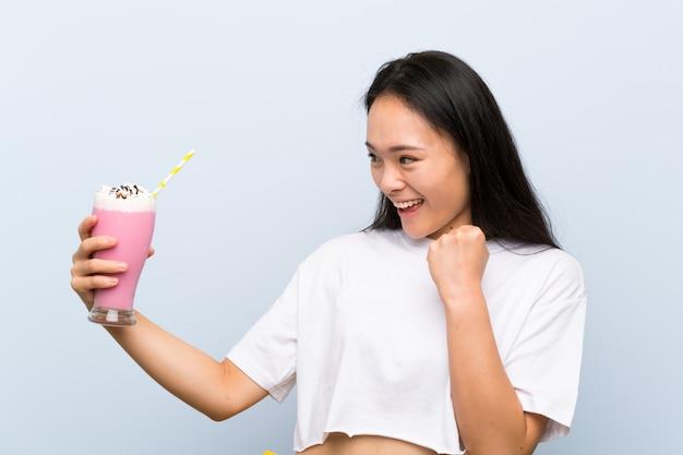 Nastolatek azjatykcia dziewczyna trzyma truskawkowego milkshake świętuje zwycięstwo