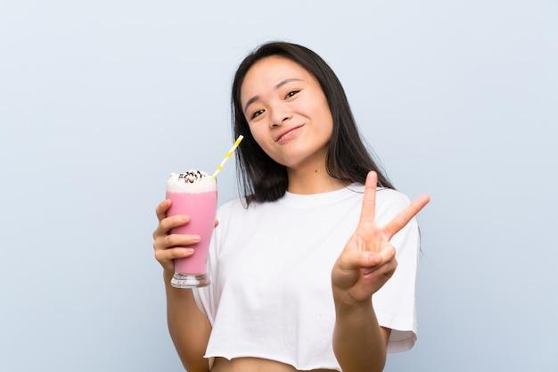 Nastolatek azjatykcia dziewczyna trzyma truskawkowego milkshake uśmiecha się zwycięstwo znaka i pokazuje
