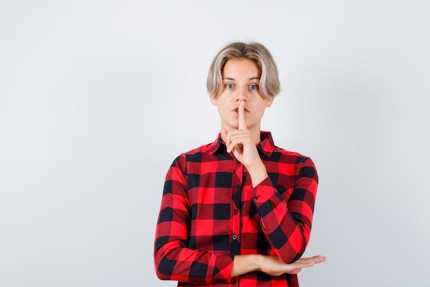 Nastolatek blond mężczyzna pokazując gest ciszy w casual shirt i patrząc skupiony, widok z przodu.