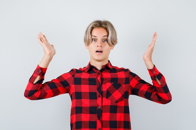 Nastolatek blond mężczyzna udając, że trzyma coś w koszuli casual i patrząc zdziwiony, widok z przodu.