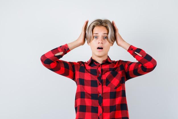Nastolatek blond mężczyzna w casual shirt z rękami w pobliżu głowy i patrząc przestraszony, widok z przodu.
