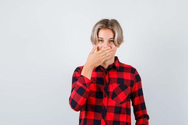 Nastolatek blond mężczyzna w koszuli dorywczo obejmujące usta ręką i patrząc wesoły, widok z przodu.