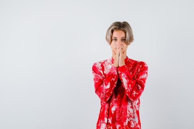 Nastolatek blond mężczyzna w przewymiarowanej koszuli z ręką w geście modlitwy i patrząc skupiony, widok z przodu.