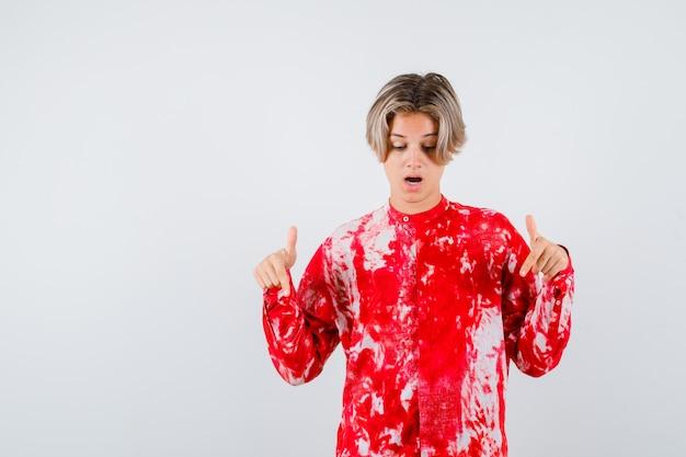 Nastolatek blond mężczyzna wskazujący w dół w przewymiarowanej koszuli i patrząc w szoku. przedni widok.