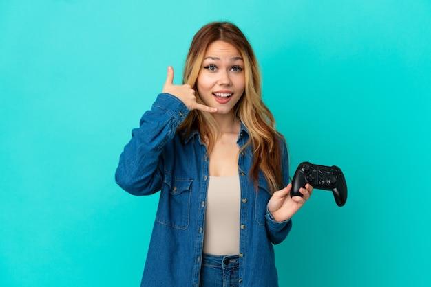 Nastolatek blondynka bawi się kontrolerem gier wideo na na białym tle ściany co telefon gest. oddzwoń do mnie znak