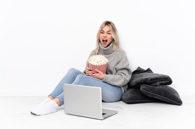 Nastolatek blondynka jedzenie popcornu podczas oglądania filmu na laptopie krzyczy do przodu z szeroko otwartymi ustami