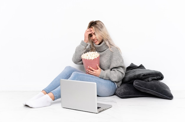 Nastolatek blondynka jedzenie popcornu podczas oglądania filmu na laptopie śmiejąc się