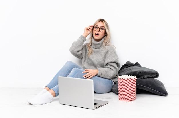 Nastolatek blondynka jedzenie popcornu podczas oglądania filmu na laptopie w okularach i zaskoczony