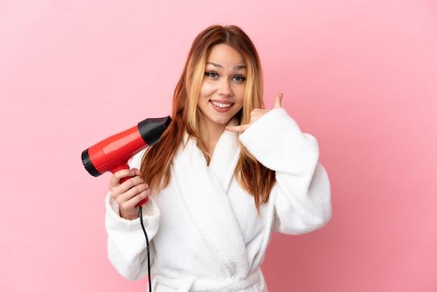 Nastolatek blondynka trzyma suszarkę do włosów na na białym tle różowy co telefon gest. oddzwoń do mnie znak