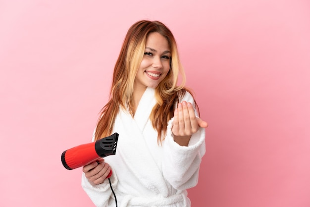 Nastolatek blondynka trzyma suszarkę do włosów na na białym tle różowym zapraszając przyjść z ręką. cieszę się, że przyszedłeś