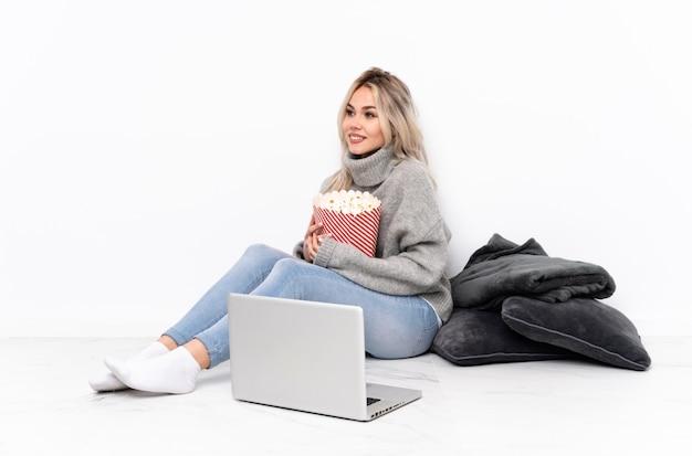 Nastolatek blondynki dziewczyny łasowania popkorn podczas gdy oglądający film na laptopie patrzeje stronę