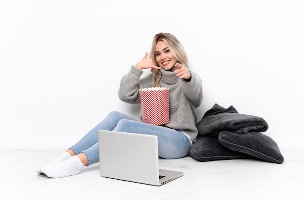 Nastolatek blondynki dziewczyny łasowania popkorn podczas gdy oglądający film na laptopie robi telefonu gestowi i wskazuje przód