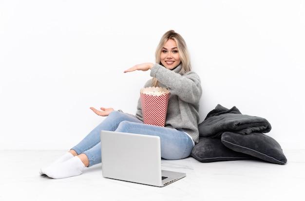 Nastolatek blondynki dziewczyny łasowania popkorn podczas gdy oglądający film na laptopie trzyma copyspace wstawiać reklamę