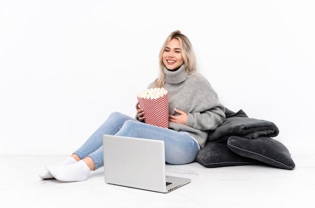 Nastolatek blondynki dziewczyny łasowania popkorn podczas gdy oglądający film na laptopie uśmiecha się dużo