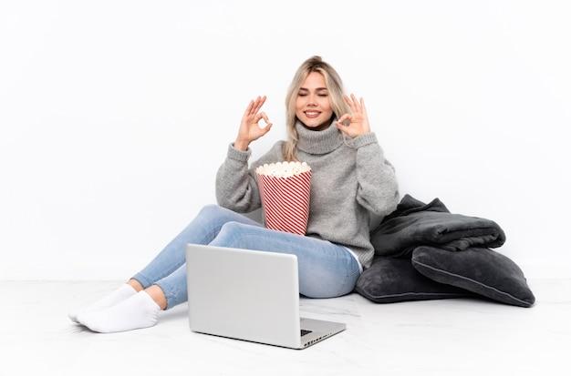 Nastolatek blondynki dziewczyny łasowania popkorn podczas gdy oglądający film na laptopie w zen pozie