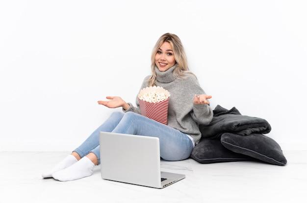 Nastolatek blondynki dziewczyny łasowania popkorn podczas gdy oglądający film na laptopu ono uśmiecha się