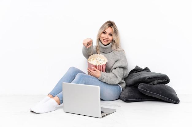 Nastolatek blondynki dziewczyny łasowania popkorn podczas gdy oglądający film na laptopu punktach dotyka z ufnym wyrażeniem