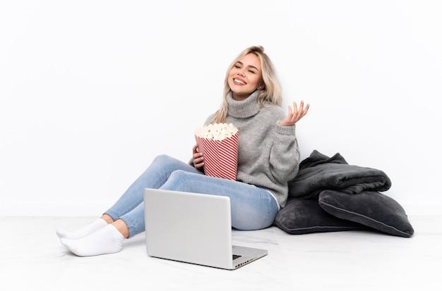 Nastolatek blondynki kobiety łasowania popkorn podczas gdy oglądający film na laptopie ono uśmiecha się dużo