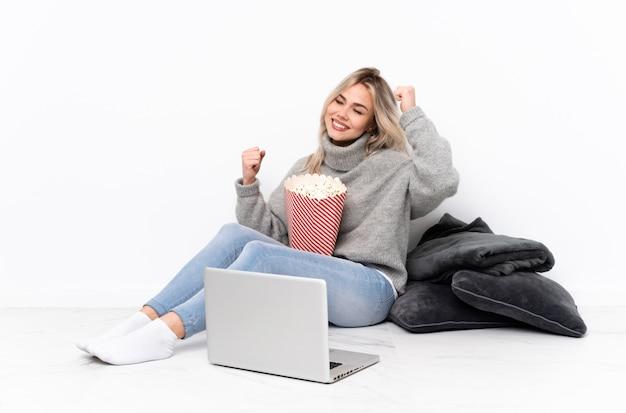 Nastolatek blondynki kobiety łasowania popkorn podczas gdy oglądający film na laptopie świętuje zwycięstwo