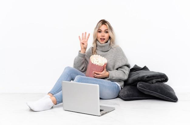 Nastolatek blondynki kobiety łasowania popkorn podczas gdy oglądający film na laptopie szczęśliwym i liczący cztery z palcami