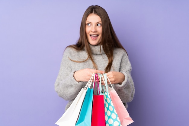 Nastolatek caucasian dziewczyna odizolowywająca na purpurach izoluje mień torba na zakupy i zaskakująca