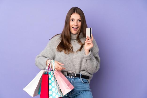 Nastolatek caucasian dziewczyna odizolowywająca na purpurowych mień torba na zakupy i zaskakujący