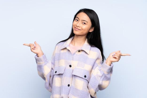 Nastolatek chinka na białym tle na niebieski palec wskazujący do boków i szczęśliwy