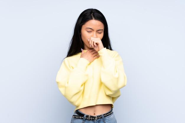 Nastolatek chinka na niebieskiej ścianie kaszel dużo