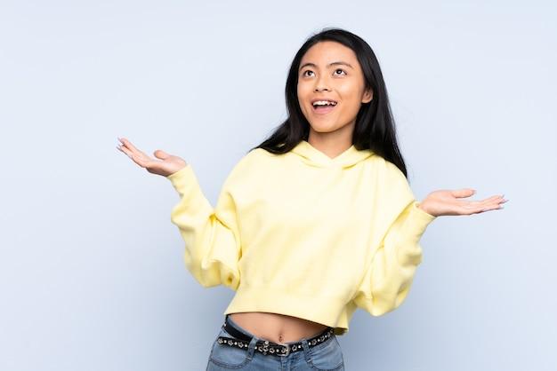 Nastolatek chinka odizolowana na niebiesko dużo uśmiecha się
