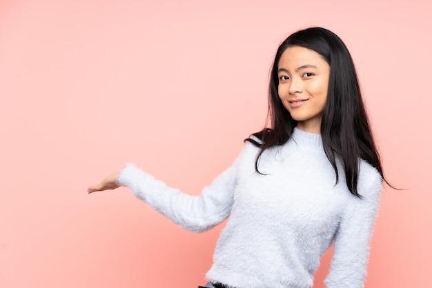 Nastolatek chinka odizolowywająca na różowym tle rozciąga ręki z boku dla zapraszać przyjeżdżać
