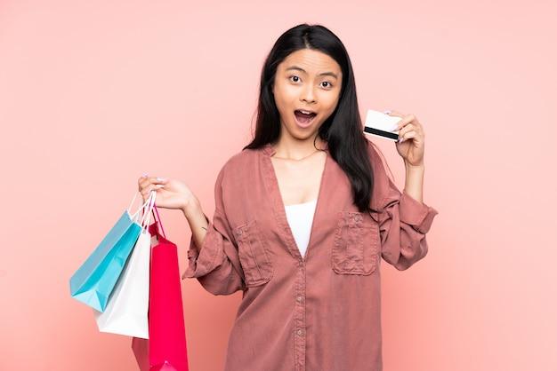 Nastolatek chińska dziewczyna na menchii ściany mienia torba na zakupy i zaskakujący