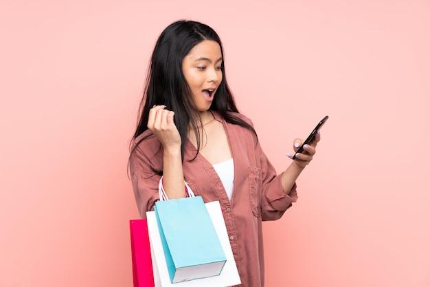 Nastolatek chińska dziewczyna na różowej ścianie trzyma torba na zakupy i pisze wiadomości z jej telefonem komórkowym przyjacielowi