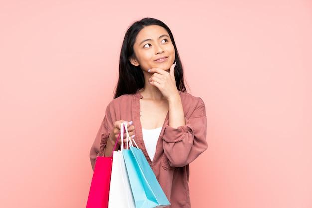 Nastolatek chińska dziewczyna odizolowywająca na menchii ściany mienia torba na zakupy i główkowaniu
