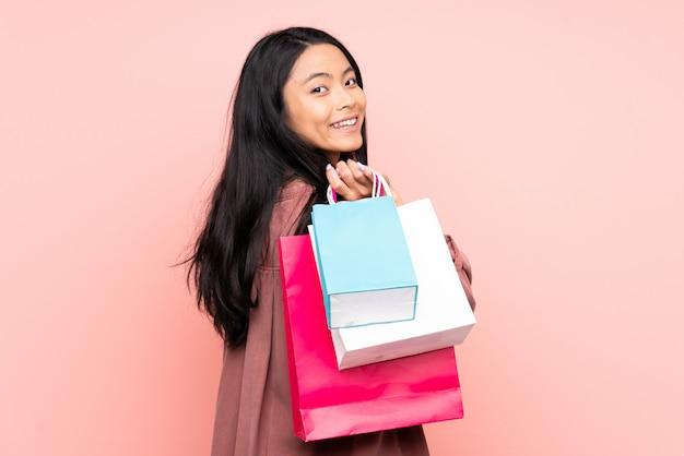 Nastolatek chińska dziewczyna odizolowywająca na menchii ściany mienia torba na zakupy i ono uśmiecha się