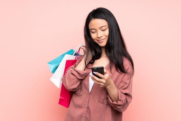 Nastolatek chińska dziewczyna odizolowywająca na menchii ściany mienia torba na zakupy i pisać wiadomości z jej telefonem komórkowym przyjaciel