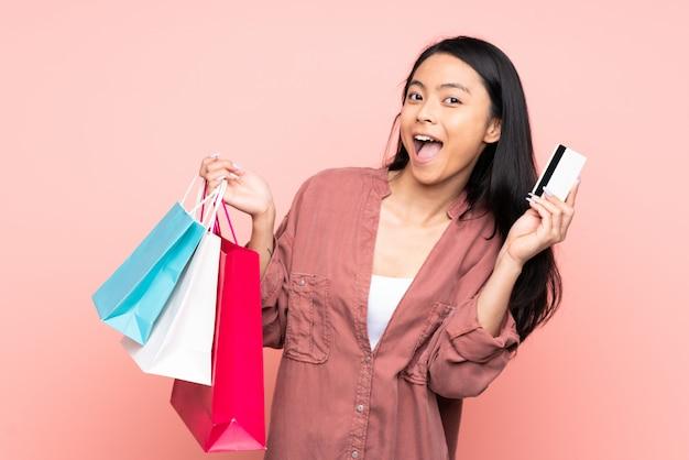 Nastolatek chińska dziewczyna odizolowywająca na różowych tła mienia torba na zakupy i karcie kredytowej