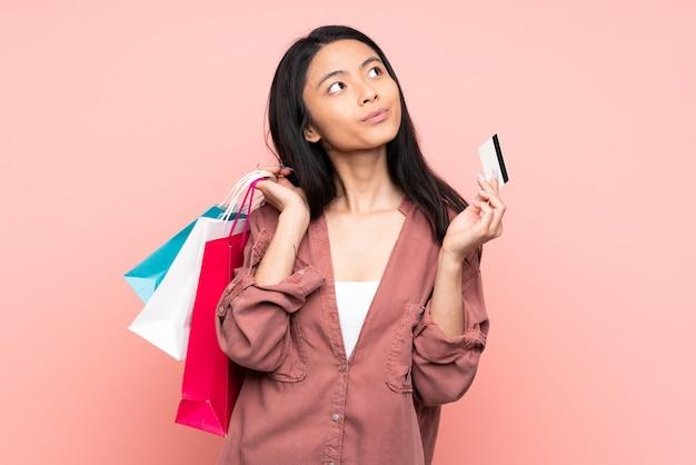 Nastolatek chińska dziewczyna odizolowywająca na różowym tła mienia torba na zakupy, karta kredytowa i główkowanie