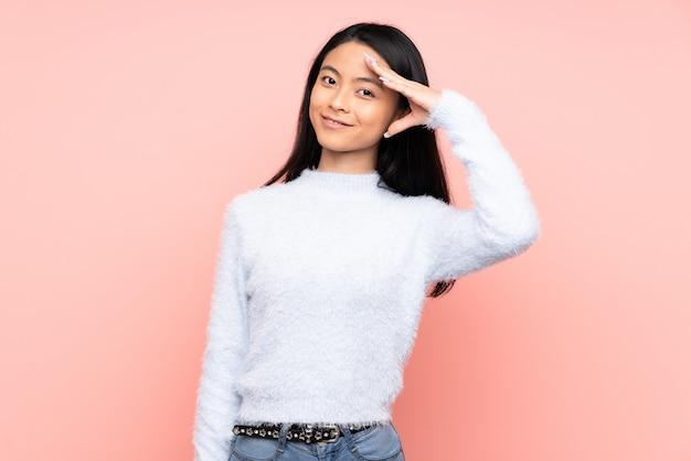 Nastolatek chińska kobieta odizolowywająca na menchii ścianie salutuje z ręką z szczęśliwym wyrażeniem