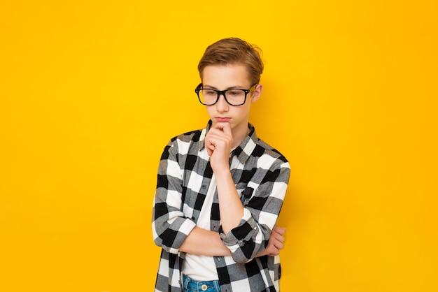 Nastolatek chłopiec na białym tle żółty z ręką na brodzie myśli o pytaniu