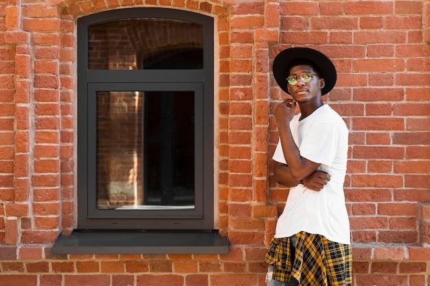 Nastolatek chłopiec pozowanie obok ściany z cegły