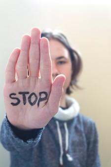 Nastolatek chłopiec robi stop bez znaku dłonią