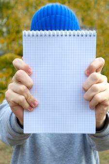 Nastolatek chłopiec trzyma stronę notesu w jego ręce na świeżym powietrzu