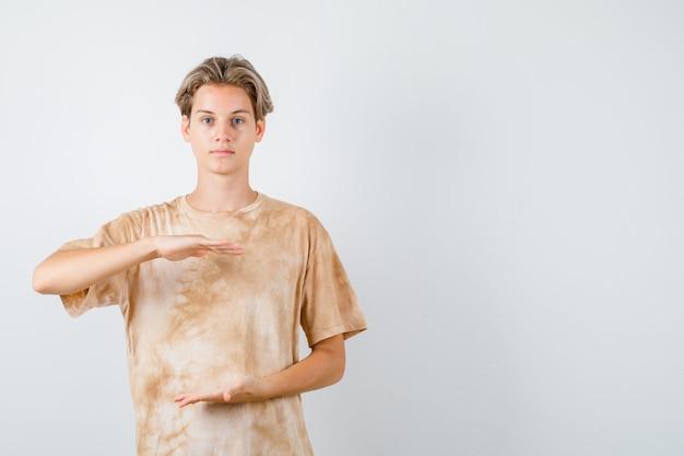 Nastolatek chłopiec w koszulce pokazujący duży znak rozmiaru i wyglądający pewnie, widok z przodu.