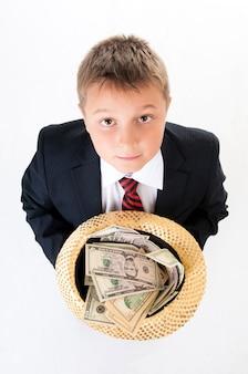Nastolatek chłopiec w szkolnym mundurku trzyma kapelusz i błaga o pieniądze.