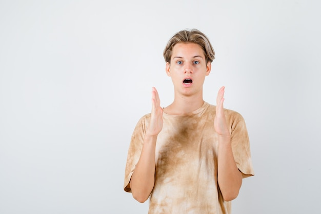 Nastolatek chłopiec w t-shirt pokazano znak rozmiaru i patrząc zaskoczony, widok z przodu.