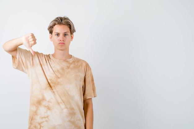 Nastolatek chłopiec w t-shirt pokazując kciuk w dół i patrząc poważnie, widok z przodu.