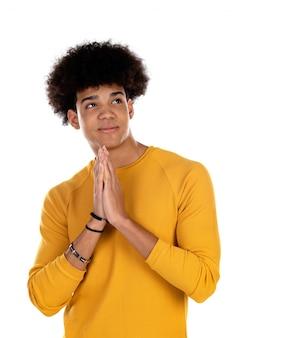 Nastolatek chłopiec z afro fryzury modleniem