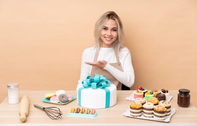 Nastolatek cukiernik z dużym ciastem w stole rozkładającym ręce na bok, zapraszając do siebie